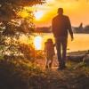 Man holding child's hand at sunset